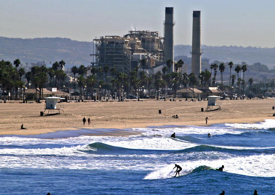 The AES Huntington Beach Generating Station forms a backdrop to surfers enjoying a spring-like November morning.  The California Coastal Commission is expected to vote this week on a proposed seawater desalination plant on a portion of the AES site.