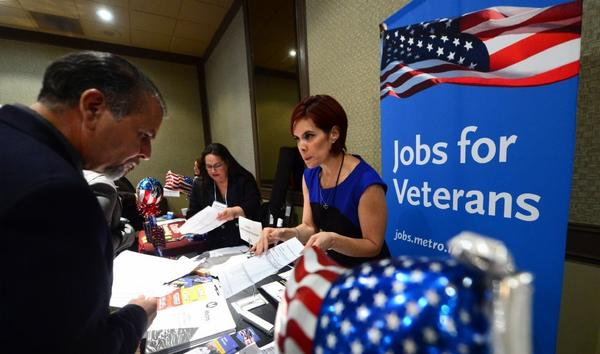"An employee from the Los Angeles County Metropolitan Transportation Authority explains and offers some forms to a Marine veteran at the annual ""Honor a Hero - Hire a Vet"" job fair in Van Nuys last month."