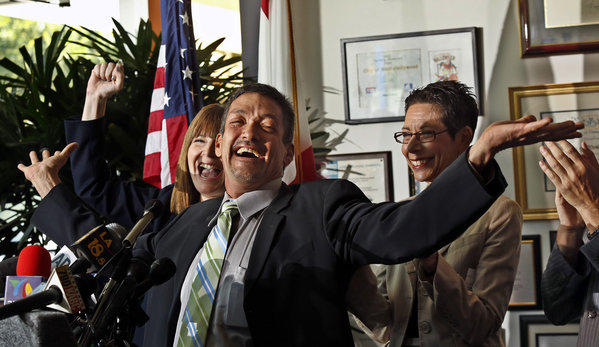 West Hollywood Councilman John Duran, center, flanked by Heid Shink from Stonewall Democrats, left, and Mayor Abbe Land celebrate the U.S. Supreme Court's decision to strike down a key part of the federal Defense of Marriage Act and overturning of California's Proposition 8. at a news conference held at City Hall.