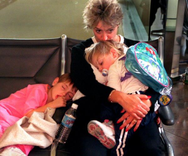 Woman and children wait at airport