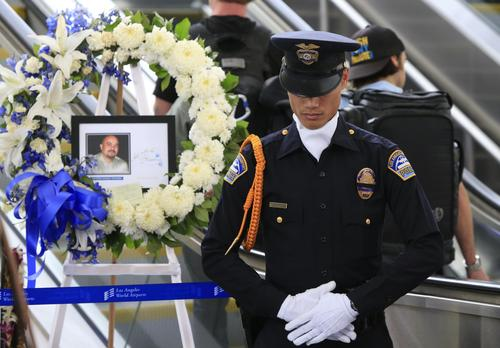 Los Angeles Airport Police Department Officer Fritz Corros stands in silence as an honor guard at the makeshift memorial to fallen TSA Officer Gerardo Hernandez.