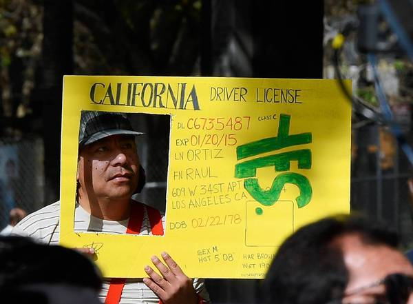 Raul Ortega holds a sign as he celebrates after Gov. Jerry Brown signed a measure allowing people in the country illegally to obtain driver's licenses.