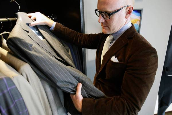 Seize sur Vingt owner James Jurney pulls out one of his suits. They make bespoke shirts and suits.