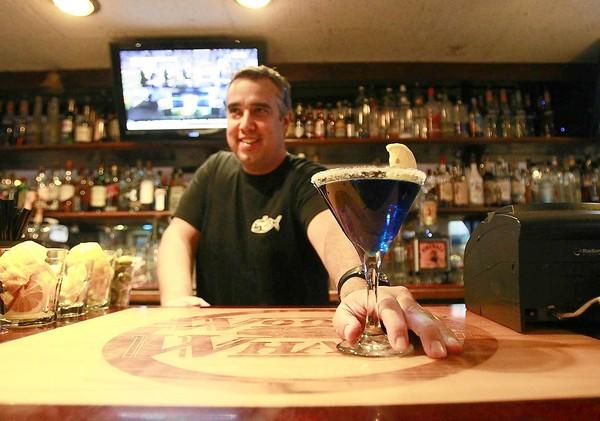 Bartender Michael Guerin serves up a fancy blue martini early on in the night at Woody's Wharf on the Balboa Peninsula.