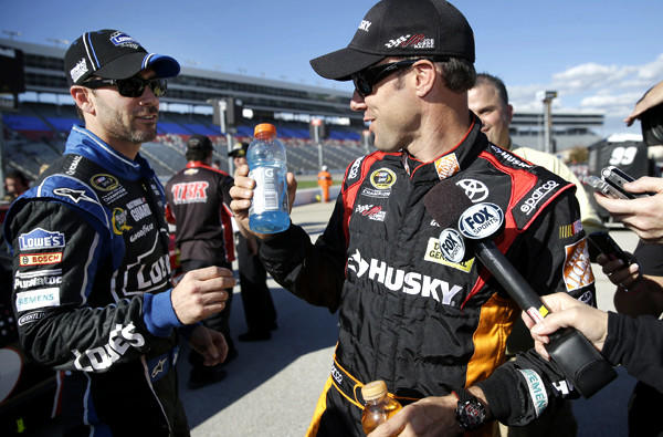 Jimmie Johnson, left, interrupts an interview by fellow NASCAR driver Matt Kenseth to hand him a drink during qualifying last week at Texas Motor Speedway.