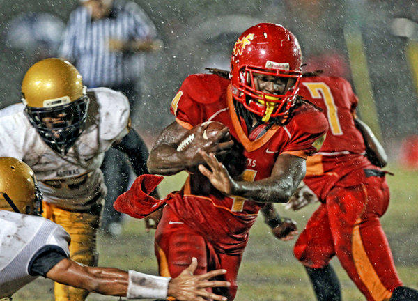 Deerfield Beach HS Brandon Powell runs for a second quarter touchdown as they play Saint Thomas Aquinas HS at Deefield Beach HS in Deerfield, November 8, 2013.