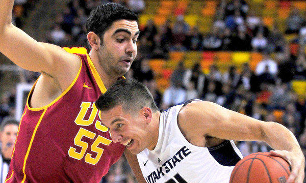 Utah State's Spencer Butterfield, right, drives around USC center Omar Oraby during the first half of the Trojans' 78-65 season-opening loss Friday.