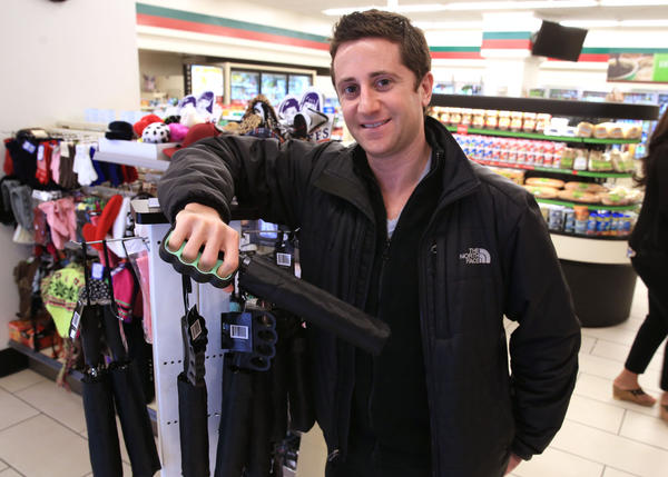 Greg Edson's company Brollytime makes an umbrella with a grip that allows a user to operate a smart phone while holding the umbrella. Brollytime is expanding into 7-Eleven stores, like this one at State Street and Illinois Street in Chicago where Edson holds an umbrella on Friday, November 1, 2013.