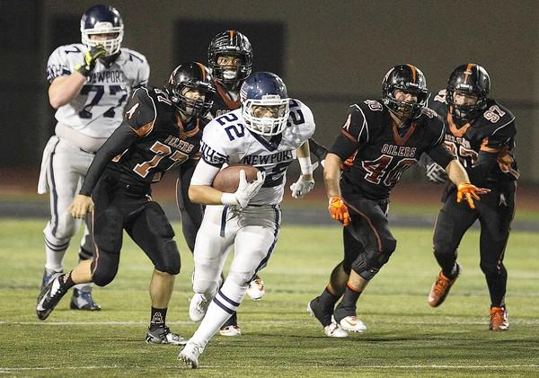 Newport Harbor's Max Durante carries the ball in the fourth quarter with a slew of Huntington Beach defenders in pursuit.
