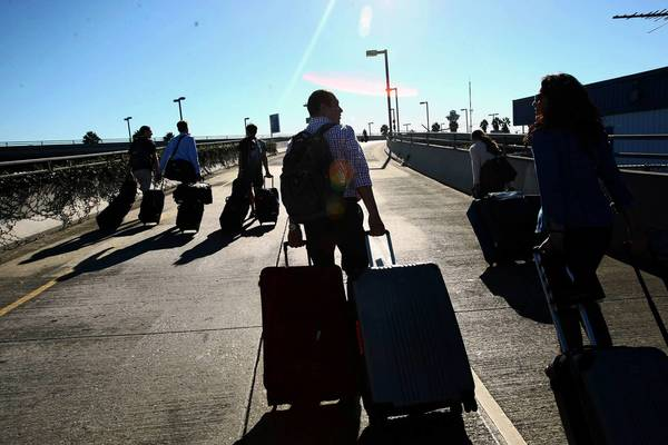 Travelers make their toward Los Angeles International Airport on Nov. 1 following the airport's closure after a gunman killed a TSA agent and wounded others.