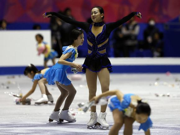 Mao Asada acknowledges the crowd that littered the ice with accolades for her as she won the NHK Trophy in Tokyo.  (Issei Kato / Reuters)