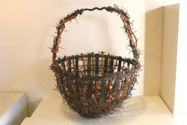 One of Karl Vidstrand's wire and branch baskets, full of barbs and thorns, at the HumanArts Gallery in Ojai. Other designs are baskets without handles, sometimes ornamented with buttons and beads.