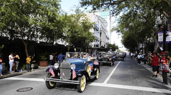 A stream of pristinely preserved antique cars carrying four Tuskegee Airman and Red Tail pilots lead the City of Orlando Veterans Day Parade down Orange Ave., Saturday, November 9, 2013. (Gary W. Green/Orlando Sentinel)