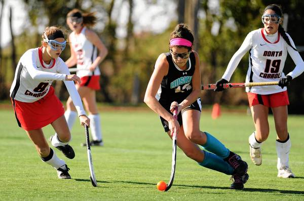 Linnea Gonzalez moves with the ball between North Carroll players Mary Guest, left, and Meghan Harmon during the Class 1A state field hockey championship game at Washington College in Chestertown on Saturday. North Carroll won the title in overtime.