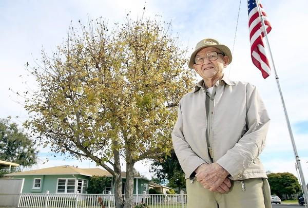 World War II veteran Thomas G. Riker, 95, poses for a portrait at his home in Eastside Costa Mesa on Thursday. Every morning, Riker hoists his American flag in his front yard. Later in the afternoon, he takes it down with proper form. He's had that routine for about 40 years.