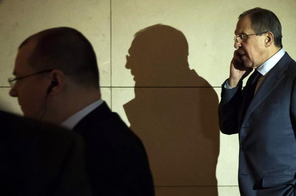 Russian Foreign Minister Sergey Lavrov (R) talks on the phone on his way to a meeting during the third day of closed-door nuclear talks in Geneva on Saturday.