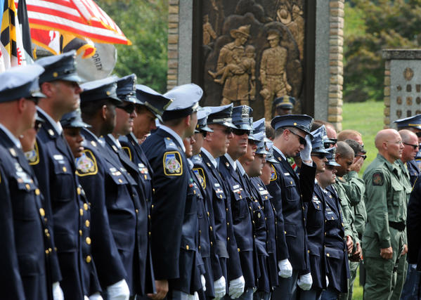 Baltimore County Police stand near the graveside of Ofc. Jason Schneider in the Fallen Heroes section of Dulaney Valley Memorial Gardens. Family, friends and law enforcement officers gather to lay to rest Officer Schneider, a member of a Baltimore County Police tactical team, who was fatally shot Wednesday while trying to serve a warrant.
