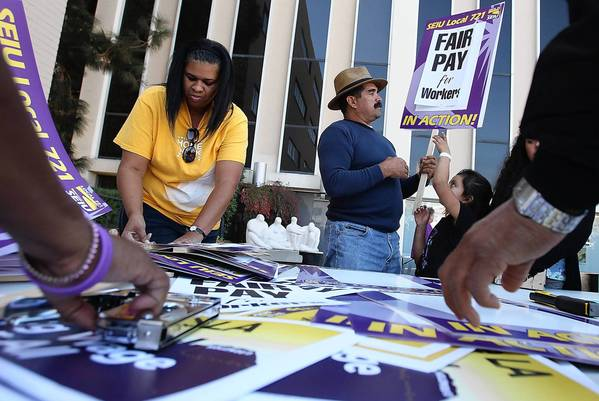 Los Angeles County employees represented by SEIU Local 721 voted Saturday to authorize a strike in case discussions with the county on healthcare, wages and working conditions do not progress. Above, SEIU members make picket signs at union headquarters downtown.