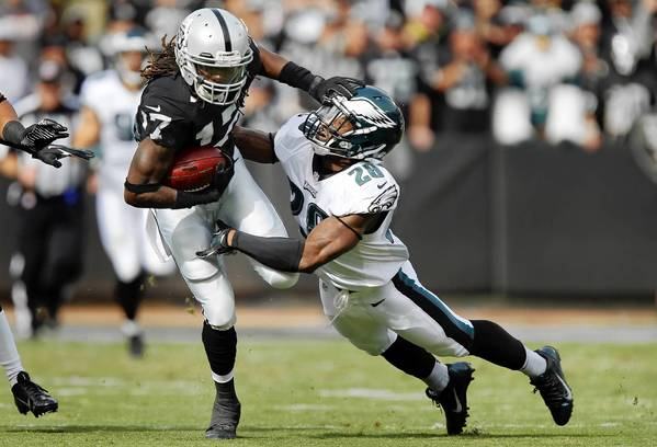 Safety Earl Wolff #28 of the Philadelphia Eagles brings down wide receiver Denarius Moore #17 of the Oakland Raiders on a 27-yard catch on the third play from scrimmage in the first quarter on November 3, 2013 at O.co Coliseum in Oakland, California.