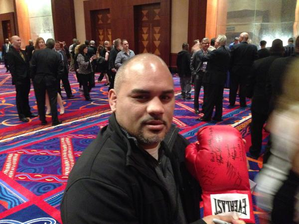 "Israel ""Pito"" Cardona poses with a glove he and his fellow members of the Connecticut Boxing Hall of Fame Class of 2013 signed."