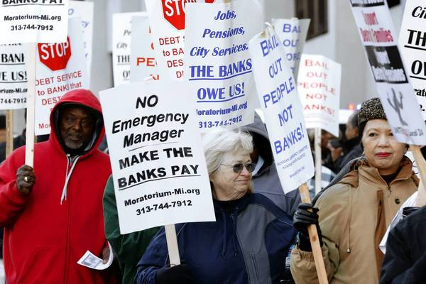 Protesters rally last month outside federal court in Detroit during a trial to determine whether the city is eligible to restructure $18 billion in debt.