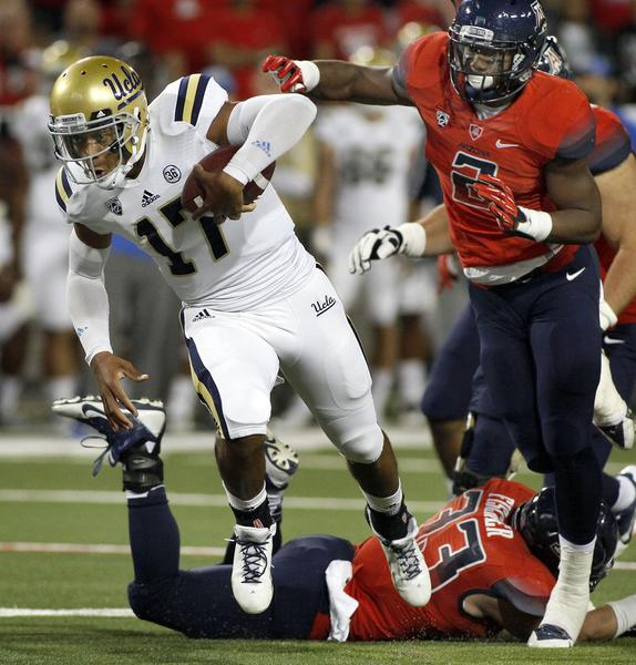 UCLA quarterback Brett Hundley runs over Arizona linebacker Marquis Flowers during the first half of the Bruins' Pac-12 Conference matchup with the Wildcats on Saturday in Tucson, Ariz.