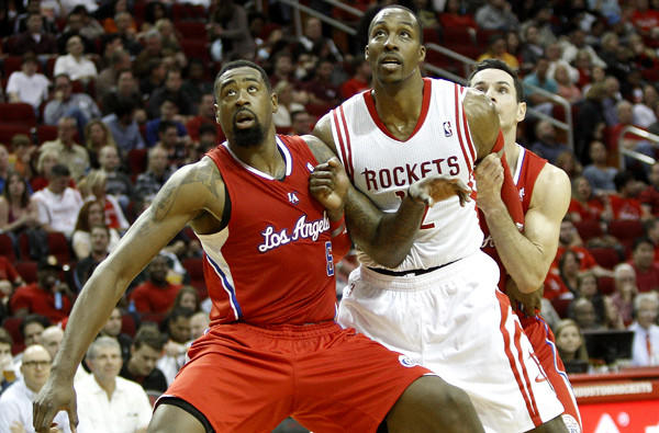 Clippers center DeAndre Jordan blocks out Rockets center Dwight Howard, with some help from teammate J.J. Redick, as they battle for rebounding position during a game Saturday night in Houston.