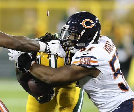 A logo flies off a helmet as Jonathan Bostic tackles the Packers' Eddie Lacy.