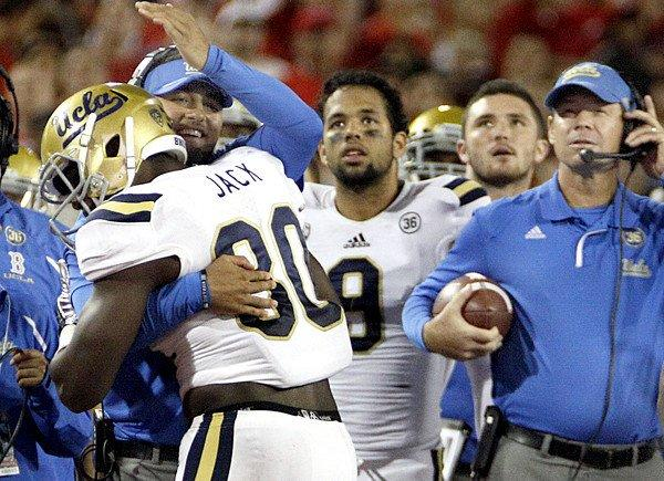 Linebacker Myles Jack, left, is congratulated by his UCLA teammates after recovering the ball in the end zone during the second half of the Bruins' 31-26 win over the Arizona Wildcats on Saturday in Tucson, Ariz.
