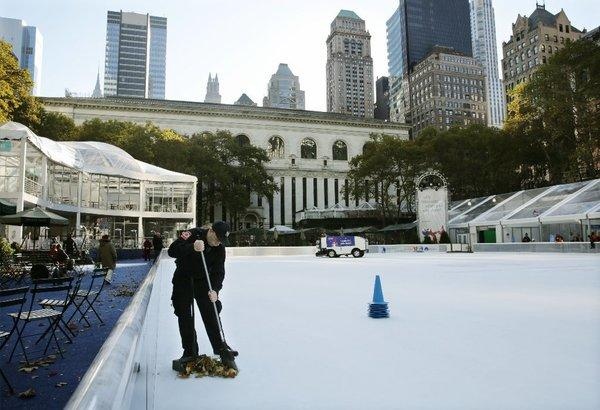 Debris is swept from the ice skating rink at Bryant Park in New York on Sunday. A shooting late Saturday sent a 14-year-old boy and 20-year-old man to the hospital.