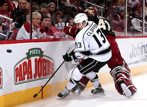 Kings forward Kyle Clifford collides with Coyotes goaltender Mike Smith as they battle for the puck behind the net during a game in Phoenix last month.