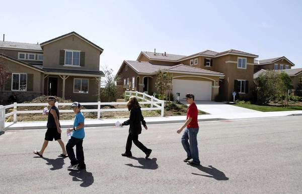 Closing on the purchase of an existing home typically takes 30 to 60 days. But with a new home, the timeline can be six months or more. Above, a family looking at model homes in San Bernardino last March.