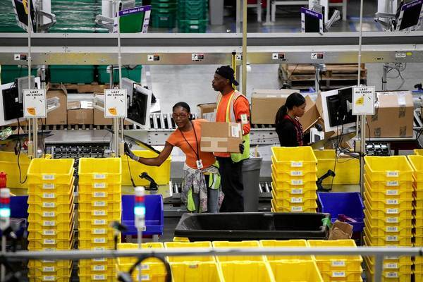 Members of Amazon.com's Prime program have free two-day shipping and, under the new deal with the U.S. Postal Service, can order items Friday and receive them Sunday. Customers outside of Prime will pay the standard shipping costs associated with business day delivery. Above, workers at Amazon's fulfillment center in San Bernardino.