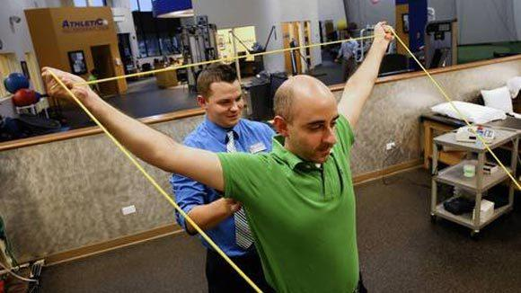 Jeremy Smith, back, a physical therapist at Athletico, works with patient  Kareem Hammad