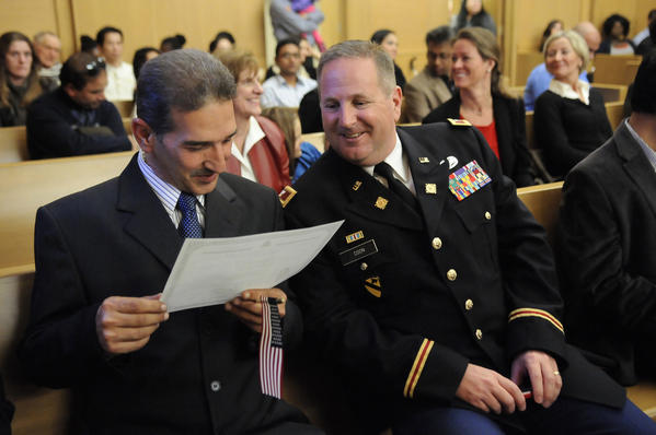 Falah Abdullatif (left) and Col. Timothy Coon (right) admire Abdullatif's citizenship certificate after he was awarded U.S. citizenship in a ceremony at the Federal Courthouse.