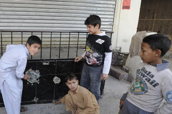 Children stand at the site where Nasiruddin Haqqani, a senior leader of the feared militant Haqqani network, was shot to death on the outskirts of Islamabad, Pakistan, on Monday.