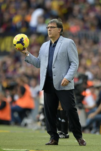 "Barcelona's Argentinian coach Gerardo ""Tata"" Martino holds a ball during the Spanish league Clasico football match FC Barcelona vs Real Madrid CF at the Camp Nou stadium in Barcelona on October 26, 2013."