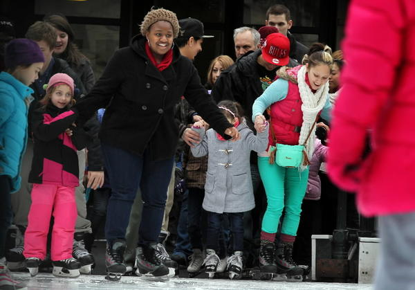 Taking advantage of the President's Day holiday, Ashley Robinson of Chicago, center, in black, races out of the gate with dozens of other ice skating enthusiast, as the gate opens up for skaters at the McCormick Tribune Ice Skating Rink in Millennium Park.