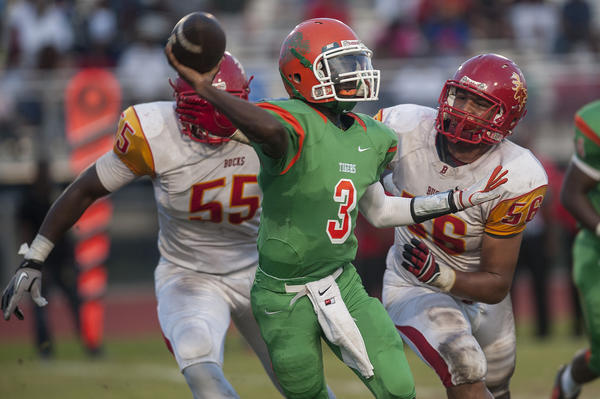 Blanche Ely quarterback Teddrick Moffet Jr. throws the ball as he is chased by Deerfield Beach's Jason Strowbridge, left, and Tyler Sayles. Both teams are in the postseason. Photo/Josh Ritchie