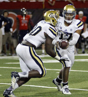 Myles Jack takes a handoff from UCLA quarterback Brett Hundley against Arizona.