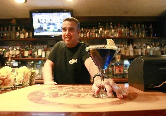 Bartender Michael Guerin serves up a fancy blue martini early in the evening at Woody's Wharf on the Balboa Peninsula.