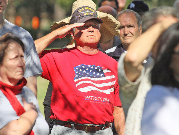 Tom Sharp, a former 60 year Burbank resident who lives in and travels in an RV and who served in the Vietnam War on the USS Ranger, salutes the flag during the singing of the Star Spangled Banner at the Veterans Day Ceremony at the McCambridge Park War Memorial in Burbank on Monday, November 11, 2013. (Tim Berger/Staff Photographer)