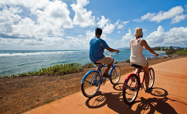 Cyclists enjoy a ride along the ocean in Kapaa on the island of Kauai. The Kauai Sands Hotel is offering a free car and free breakfast through Dec. 24.
