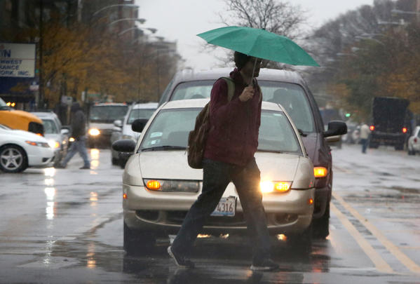 A man uses his umbrella to protect herself from the mixture of  rain and snow as he crosses Ashland Ave. at North Ave. in Chicago.