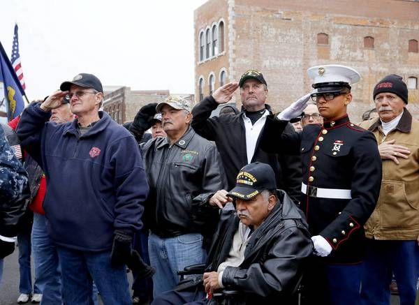 Vietnam war veterans salute during the national anthem during a parade in Aurora. Gary Pennington (Navy), from left, Dennis Galloway (Army), John Aister (Marine), John I. Acosta (new Marine), Larry Nyman (Marine) and John J. Acosta (Army), the grandfather of John I. Acosta. The city of Aurora held a Veterans Day parade and an Honoring All Who Served ceremony.