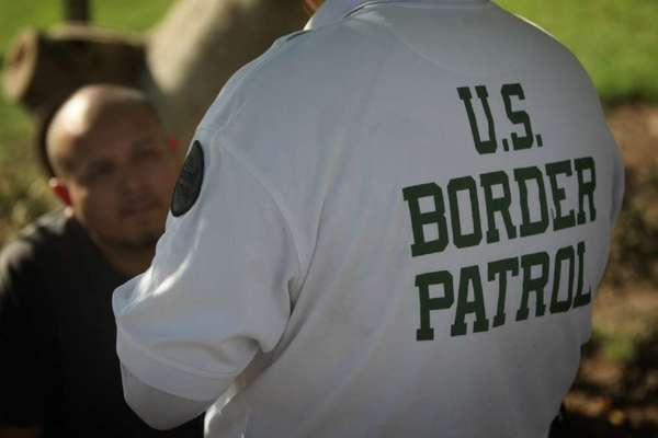 A U.S. Border Patrol officer questions a man in Friendship Park across the street from the Calexico, Calif. port of entry.