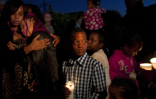 Tears stream down the face of 10-year-old James Dotson at a vigil Monday for his cousin Elawnza Peebles, 14, who was fatally shot as he was walking home Saturday evening.