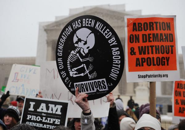 Antiabortion and pro-choice placards are seen in front of the Supreme Court.