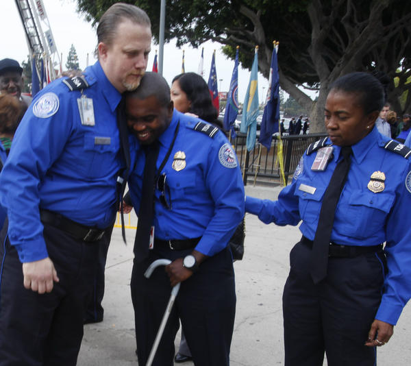 Wounded TSA Officer Tony Grigsby, center, is greeted by fellow officers as he arrives for the public memorial service for slain Transportation Security Administration agent Gerardo Hernandez at the Los Angeles Sports Arena on Tuesday.