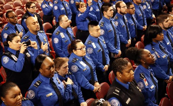 Transportation Security Administration officers stand together during the public memorial service for slain TSA agent Gerardo Hernandez at the Los Angeles Sports Arena on Tuesday.